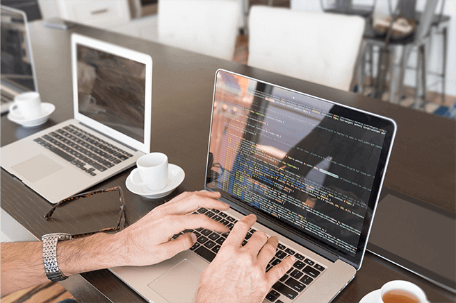 over-the-shoulder-view-of-hands-typing-on-laptop-computer-keyboard-writing-code-with-coffee-tea_t20_R6JN1k